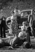 """GB. England. Beaulie Jazz Festival. As youngsters embraced on the village green the locals behaved like tourists, fascinated by their """"lewd"""" behaviour. Liberation started with the young and in this setting it was a novelty. 1961."""
