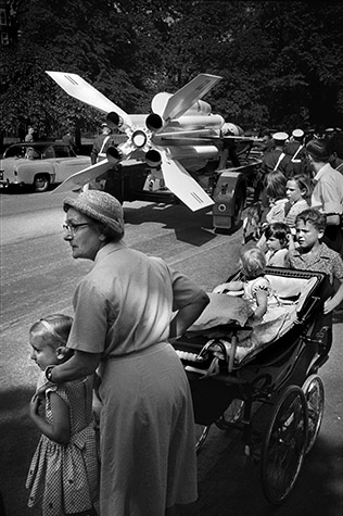 GB. ENGLAND. Nanny watching Military Parade passing down the Mall. Armed forces are always eager to brandish their latest purchases, by which some members of the public are possibly reassured.1960