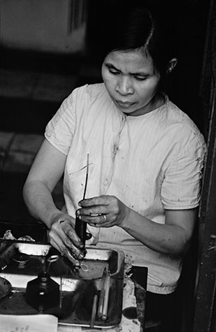 VIET NAM. Ha Noi. Refilling ball-point refills with a home-made ink from a syringe on a Ha Noi street corner.