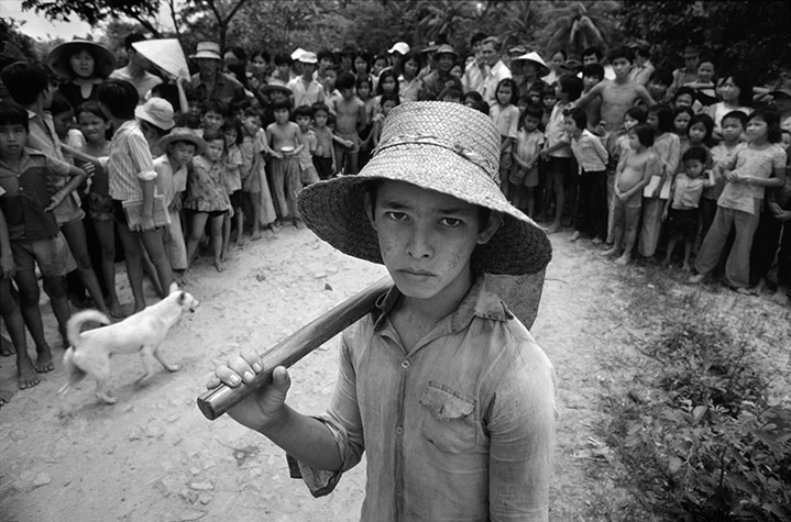"VIETNAM. Vietnam at Peace. Cuanh nicknamed ""Cu Teo"" lived with his ""grandparents"", Tra Van Bao and Tran Dhi Hang, on their small plot of land about 10 kilometres north of Ben Tre. He does the same agricultural work as all the other peasants in the area and left school for the fields because the other children taunted him. Cuanh, when five year-old, abandoned by his mother in a forest during the withdrawal from Kontum in the last days of the war in 1975. The grandparents' son, an ARVN soldier, who brought him to Ben Tre, found him. After the war some ""people"" from Saigon came to Ben Tre to buy Amerasian children but the ""grandparents"" refused to sell the boy. On my arrival Cuanh ran away and his grandmother was visibly shaken until she was reassured that I was not there to take away the boy. 1985."