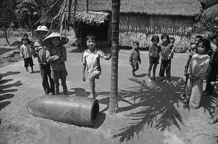 VIET NAM. Children with an unexploded bomb in the courtyard of their house in a village near Vinh.