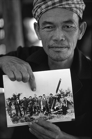 VIET NAM. Mr. Vo Van Chung, veteran NLF soldier with photograph of himself and comrades with a downed US helicopter they shot down near Cu Chi on the 19th April 1971.