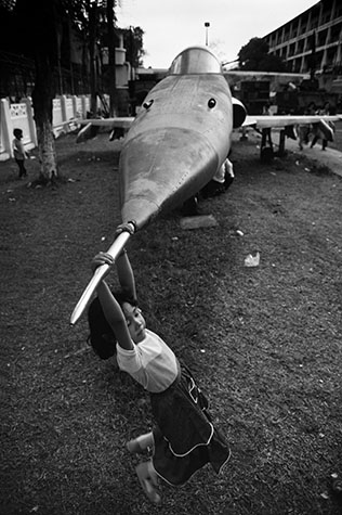 VIET NAM. Ho Chi Minh City. At the History Museum a girl swings on the nose of a fighter jet.