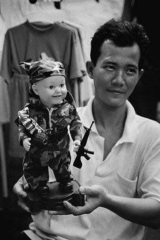 VIET NAM. 2002. American visitors to Viet Nam are always surprised by the lack of animosity towards them. This salesman is demonstrating a dancing, smiling GI Joe complete with his M16 rifle and hand grenade, to bewildered tourists and local people.