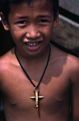 PHILIPPINES. Religion in the Philippines. Boy wearing a crucifix suitably crafted from bullets. 1981.