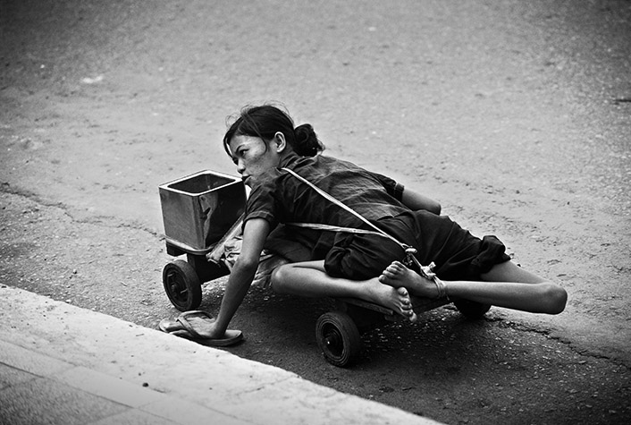 VIETNAM. Ho Chi Minh City. A woman wheeling herself through the street. 1980