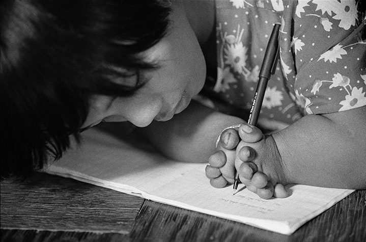 VIETNAM. Cam Nghia. LE THI Hoa, fourteen, born stunted with deformed fingers, proudly demonstrates her excellent penmanship. 1998.