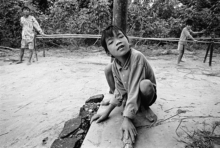 VIETNAM. Cam Nghia. 1998. TRAN Van Lam, ten, is mentally retarded and has difficulty walking. His older brothers, TRAN Van Thuan and TRAN Van Hoang also suffer from malformed legs. Their father built them a bamboo walkway to help strengthen their limbs.