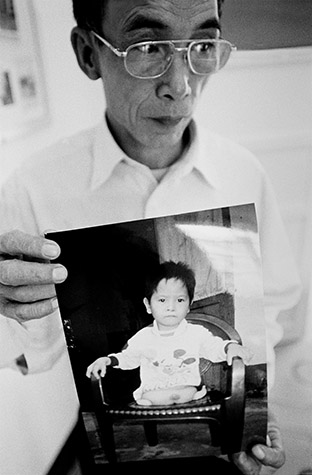 VIETNAM. Hanoi. NGUYEN Tien Nhung is vice-director at the Friendship Village. He is holding a photograph of six-year-old To Thanh Nam. His father fought in the war. He received a wheelchair and was able to return home. 2002