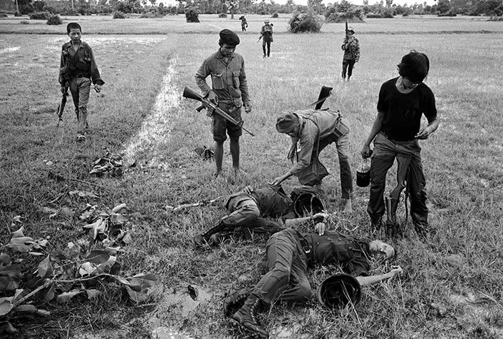 CAMBODIA. After an ambush, soldiers returned to recover their dead.  Pockets of the fallen were first checked for cash since Cambodian soldiers were rarely paid.  This one found enough to buy his way out of the army. 1973