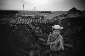 VIET NAM. Young scrap-collector in front of pile of shell casings at the Camp Evans site near Hue.