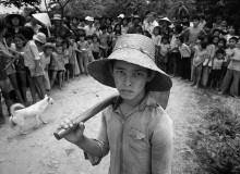 """VIETNAM. Vietnam at Peace. Cuanh nicknamed """"Cu Teo"""" lived with his """"grandparents"""", Tra Van Bao and Tran Dhi Hang, on their small plot of land about 10 kilometres north of Ben Tre. He does the same agricultural work as all the other peasants in the area and left school for the fields because the other children taunted him. Cuanh, when five year-old, abandoned by his mother in a forest during the withdrawal from Kontum in the last days of the war in 1975. The grandparents' son, an ARVN soldier, who brought him to Ben Tre, found him. After the war some """"people"""" from Saigon came to Ben Tre to buy Amerasian children but the """"grandparents"""" refused to sell the boy. On my arrival Cuanh ran away and his grandmother was visibly shaken until she was reassured that I was not there to take away the boy. 1985."""
