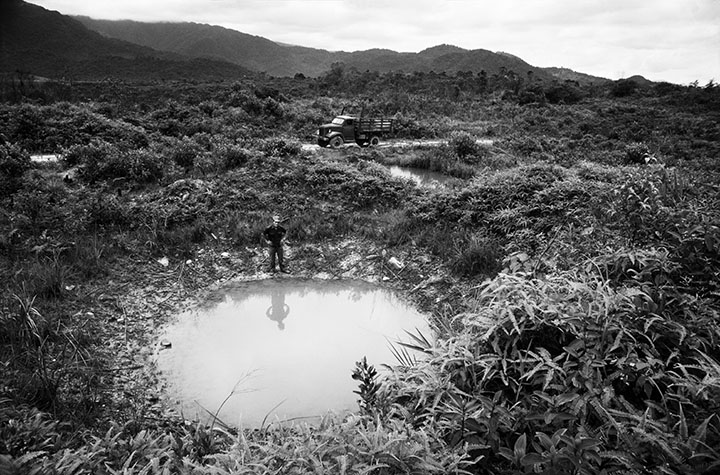VIET NAM. On a part of the trail that passes through the A Shau valley a driver who spent seven years traversing this section during the war stands near a crater made by a bomb that narrowly missed his lorry in 1971.