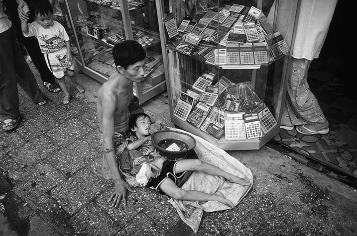 VIET NAM. Ha Noi. Father and son begging on the street.