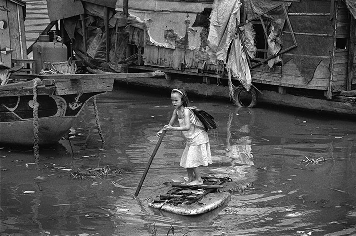 VIET NAM. 2002. This girl lives with her family on their boat moored on the Saigon River. To get to school, she punts herself to the bank standing on a piece of Styrofoam packing material.