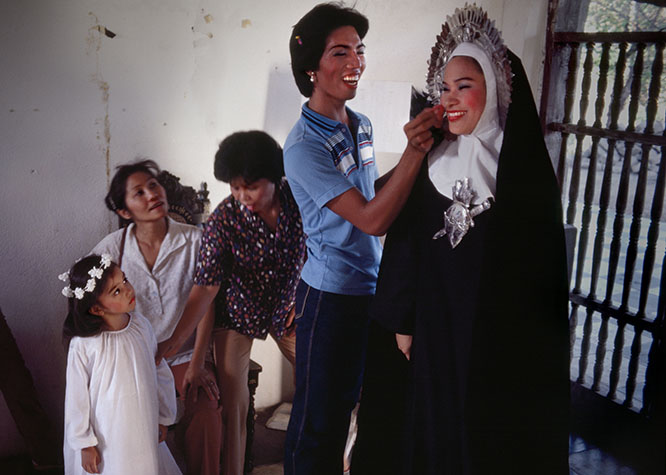 PHILIPPINES. Religion in the Philippines. A transvestite prepares his fellow transvestite with makeup for his role as a nun. 1981.
