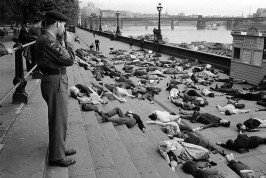 Anti-H bomb protest. To illustrate the fatalities from a nuclear attack a group of people adopted positions of death along the Thames Embankment early one Sunday morning. A bemused soldier paused to observe the event. 1962.