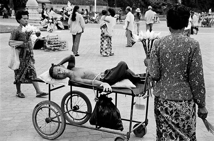 VIETNAM. Phnom Penh. OUM Sokhon, 25, born in Sa Ang district, Kandal Province, waits for donations amongst the flower sellers. His mother has died and his father stays with monks in a pagoda in Sa Ang.2001