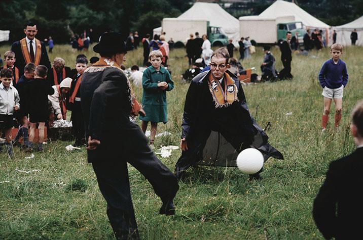 Orange boys playing footie. Ireland. Drogheda. 1965.